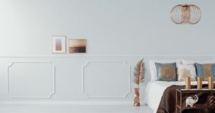 Χρυσός λαμπτήρας επάνω από ένα κρεβάτι στο φωτεινό εσωτερικό κρεβατοκάμαρων με τη χρυσή πολυθρόνα βίντεο φιλμ μικρού μήκους