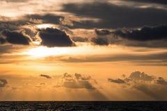 Χρυσός νεφελώδης ουρανός ηλιοβασιλέματος με τη σκιά πέρα από τη σκοτεινή θάλασσα Στοκ εικόνα με δικαίωμα ελεύθερης χρήσης