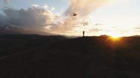 Χρυσός ουρανός ηλιοβασιλέματος βουνών σκιαγραφιών γυναικών που πετά το με μακριά ουρά ικτίνο παιχνιδιών 4k σε αργή κίνηση απόθεμα βίντεο