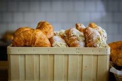 Χρυσός που ψήνεται πρόσφατα croissants σε ένα καλάθι αχύρου σε μια γκρίζα πλάτη στοκ εικόνα με δικαίωμα ελεύθερης χρήσης