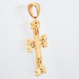 Χρυσός σταυρός κρεμαστών κοσμημάτων με το πανόραμα πετρών κόκκινου φωτός Στοκ Εικόνες