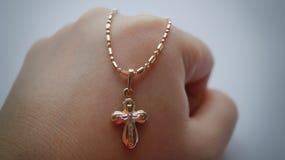 Χρυσός σταυρός σε μια χρυσή αλυσίδα σε μια πυγμή στοκ φωτογραφία