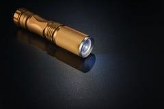 Χρυσός φακός στη σκοτεινή επιφάνεια Στοκ Εικόνες