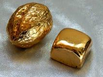 Χρυσός φραγμός με ένα καρύδι από το χρυσό φύλλο σε ένα άσπρο υπόβαθρο Στοκ εικόνες με δικαίωμα ελεύθερης χρήσης