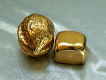 Χρυσός φραγμός με ένα καρύδι από το χρυσό φύλλο σε ένα άσπρο υπόβαθρο Στοκ φωτογραφία με δικαίωμα ελεύθερης χρήσης
