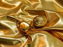 Χρυσός φραγμός με ένα καρύδι από το χρυσό φύλλο σε ένα χρυσό υπόβαθρο Στοκ φωτογραφία με δικαίωμα ελεύθερης χρήσης