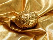 Χρυσός φραγμός με ένα καρύδι από το χρυσό φύλλο σε ένα χρυσό υπόβαθρο Στοκ Φωτογραφία