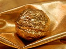 Χρυσός φραγμός με ένα καρύδι από το χρυσό φύλλο σε ένα χρυσό υπόβαθρο Στοκ εικόνες με δικαίωμα ελεύθερης χρήσης