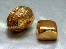 Χρυσός φραγμός με τα καρύδια ξύλων καρυδιάς σε ένα αργυροειδές υπόβαθρο Στοκ εικόνα με δικαίωμα ελεύθερης χρήσης