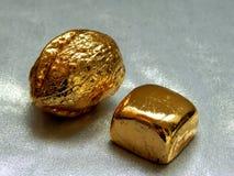 Χρυσός φραγμός με τα καρύδια ξύλων καρυδιάς σε ένα αργυροειδές υπόβαθρο Στοκ Εικόνες
