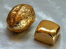 Χρυσός φραγμός με τα καρύδια ξύλων καρυδιάς σε ένα αργυροειδές υπόβαθρο Στοκ φωτογραφία με δικαίωμα ελεύθερης χρήσης