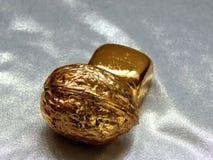 Χρυσός φραγμός με τα καρύδια ξύλων καρυδιάς σε ένα αργυροειδές υπόβαθρο Στοκ Εικόνα