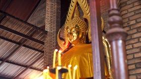 Χρυσό άγαλμα του Βούδα με το θολωμένο φως κεριών στο πρώτο πλάνο στοκ εικόνα