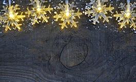 χρυσό απομονωμένο λευκό κορδελλών δώρων Χριστουγέννων κιβωτίων συνόρων ανασκόπησης Snowflakes φω'τα γιρλαντών στο παλαιό ξύλινο α Στοκ Φωτογραφίες