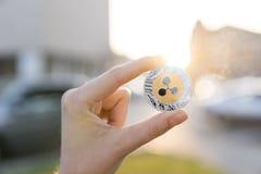 Χρυσό ασημένιο νόμισμα κυματισμών υπό εξέταση σε ένα θολωμένο υπόβαθρο ηλιοβασιλέματος Χέρι που κρατά crypto εικονικά χρήματα νομ Στοκ εικόνες με δικαίωμα ελεύθερης χρήσης
