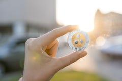 Χρυσό ασημένιο νόμισμα κυματισμών υπό εξέταση σε ένα θολωμένο υπόβαθρο ηλιοβασιλέματος Χέρι που κρατά crypto εικονικά χρήματα νομ Στοκ Εικόνες