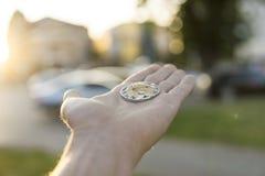 Χρυσό ασημένιο νόμισμα κυματισμών υπό εξέταση σε ένα θολωμένο υπόβαθρο ηλιοβασιλέματος Χέρι που κρατά crypto εικονικά χρήματα νομ Στοκ Φωτογραφία