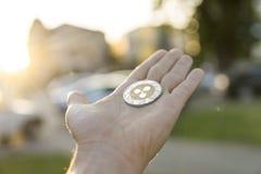 Χρυσό ασημένιο νόμισμα κυματισμών υπό εξέταση σε ένα θολωμένο υπόβαθρο ηλιοβασιλέματος Χέρι που κρατά crypto εικονικά χρήματα νομ Στοκ φωτογραφίες με δικαίωμα ελεύθερης χρήσης