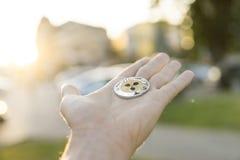 Χρυσό ασημένιο νόμισμα κυματισμών υπό εξέταση σε ένα θολωμένο υπόβαθρο ηλιοβασιλέματος Χέρι που κρατά crypto εικονικά χρήματα νομ Στοκ εικόνα με δικαίωμα ελεύθερης χρήσης
