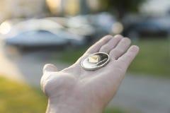 Χρυσό ασημένιο νόμισμα Ethereum υπό εξέταση σε ένα θολωμένο υπόβαθρο ηλιοβασιλέματος Χέρι που κρατά crypto εικονικά χρήματα νομίσ Στοκ Φωτογραφία