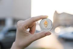 Χρυσό ασημένιο νόμισμα Ethereum υπό εξέταση σε ένα θολωμένο υπόβαθρο ηλιοβασιλέματος Χέρι που κρατά crypto εικονικά χρήματα νομίσ Στοκ φωτογραφίες με δικαίωμα ελεύθερης χρήσης