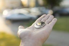 Χρυσό ασημένιο νόμισμα Ethereum υπό εξέταση σε ένα θολωμένο υπόβαθρο ηλιοβασιλέματος Χέρι που κρατά crypto εικονικά χρήματα νομίσ Στοκ Εικόνες