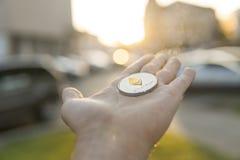 Χρυσό ασημένιο νόμισμα Ethereum υπό εξέταση σε ένα θολωμένο υπόβαθρο ηλιοβασιλέματος Χέρι που κρατά crypto εικονικά χρήματα νομίσ Στοκ φωτογραφία με δικαίωμα ελεύθερης χρήσης