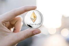 Χρυσό ασημένιο νόμισμα Ethereum υπό εξέταση σε ένα θολωμένο υπόβαθρο ηλιοβασιλέματος Χέρι που κρατά crypto εικονικά χρήματα νομίσ Στοκ εικόνα με δικαίωμα ελεύθερης χρήσης