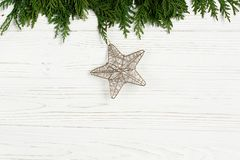 Χρυσό αστέρι Χριστουγέννων στους πράσινους κλάδους δέντρων στο μοντέρνο άσπρο RU Στοκ Εικόνα
