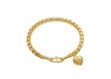 Χρυσό βραχιόλι με ένα κρεμαστό κόσμημα μορφής καρδιών Στοκ Εικόνες