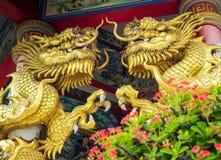 Χρυσό γλυπτό δράκων και κόκκινο λουλούδι του αγκαθιού Χριστού στα κινέζικα Στοκ Φωτογραφίες
