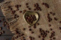 Χρυσό δάπεδο τζακιού-διαμορφωμένο πιατάκι με τα ψημένα φασόλια καφέ Στοκ Εικόνες