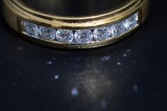 Χρυσό δαχτυλίδι με τα διαμάντια στο πίσω υπόβαθρο στοκ φωτογραφία με δικαίωμα ελεύθερης χρήσης