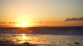 Χρυσό ηλιοβασίλεμα με τα κύματα στην παραλία απόθεμα βίντεο