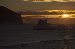 Χρυσό ηλιοβασίλεμα με τις σκιαγραφίες παγόβουνων Στοκ Εικόνες