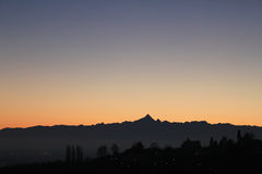 Χρυσό ηλιοβασίλεμα πέρα από το λόφο και τον ορίζοντα βουνών στοκ εικόνες με δικαίωμα ελεύθερης χρήσης