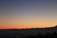 Χρυσό ηλιοβασίλεμα πέρα από το λόφο και τον ορίζοντα βουνών στοκ εικόνα με δικαίωμα ελεύθερης χρήσης