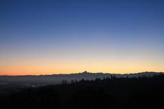 Χρυσό ηλιοβασίλεμα πέρα από το λόφο και τον ορίζοντα βουνών στοκ εικόνα