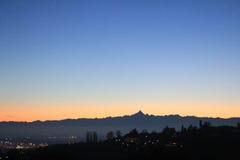 Χρυσό ηλιοβασίλεμα πέρα από το λόφο και τον ορίζοντα βουνών στοκ φωτογραφία