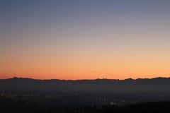 Χρυσό ηλιοβασίλεμα πέρα από το λόφο με τον ορίζοντα βουνών στοκ φωτογραφία