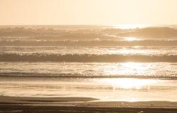 Χρυσό ηλιοβασίλεμα στην παραλία με τα κύματα Στοκ Φωτογραφίες