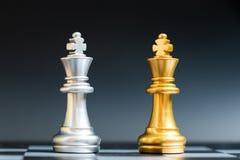Χρυσό και ασημένιο πρόσωπο κομματιού σκακιού βασιλιάδων στη σκακιέρα στοκ εικόνα με δικαίωμα ελεύθερης χρήσης