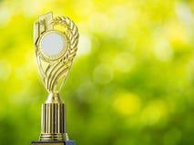 Χρυσό κερδίζοντας τρόπαιο βραβείων με το αφηρημένο υπόβαθρο του φυσικού φωτός bokeh από τα φύλλα Στοκ Εικόνες