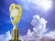 Χρυσό κερδίζοντας τρόπαιο βραβείων στο υπόβαθρο μπλε ουρανού και ήλιων Στοκ Φωτογραφίες