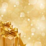 Χρυσό κιβώτιο δώρων στην αφηρημένη χρυσή ανασκόπηση Στοκ Εικόνα