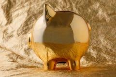 Χρυσό κιβώτιο χρημάτων χοίρων σε μια χρυσή έννοια υποβάθρου για την οικονομική ασφάλεια, την προστασία, την ασφαλείς επένδυση ή τ στοκ φωτογραφία με δικαίωμα ελεύθερης χρήσης