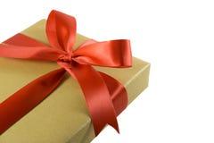 Χρυσό κιβώτιο δώρων με το κόκκινο τόξο κορδελλών Στοκ Εικόνες