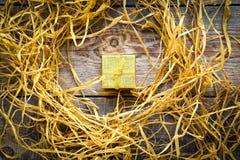Χρυσό κιβώτιο δώρων στον ξύλινο πίνακα με raffia ή το σπάγγο Στοκ Εικόνες
