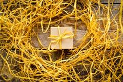 Χρυσό κιβώτιο δώρων στον ξύλινο πίνακα με raffia ή το σπάγγο Στοκ Φωτογραφία