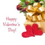 Χρυσό κιβώτιο δώρων, δύο κόκκινα καρδιές και λουλούδια, που απομονώνονται Στοκ Εικόνες